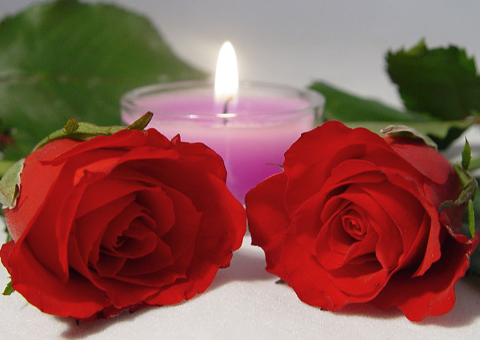 Romance - red roses and a candle depicting a romantic setting. Romance - red roses and a candle depicting a romantic setting.  Photo: BigStockPhoto.com | kjpargeter